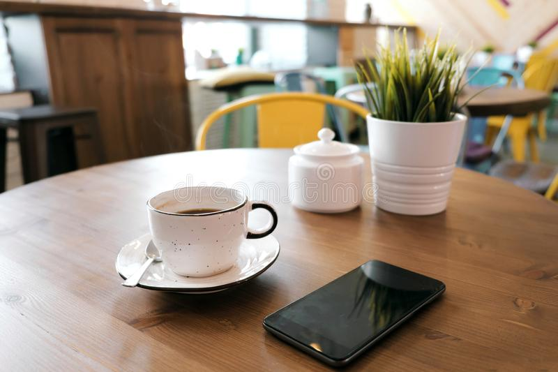 Coffee drink on wooden table with blur cafeteria as background. A white clay cup with coffee stands on a wooden table, next to it is a smartphone and a green royalty free stock photos