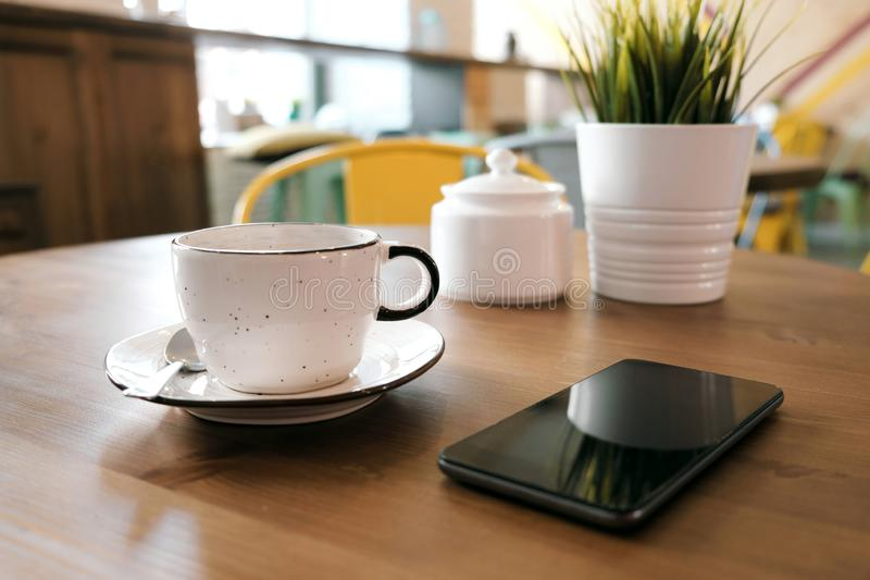 Coffee drink on wooden table with blur cafeteria as background. A white clay cup with coffee stands on a wooden table, next to it is a smartphone and a green royalty free stock images