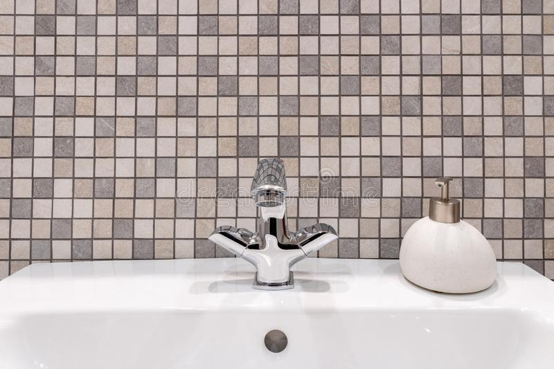 White clean bathroom sink with shiny faucet and stone soap dish. stock image