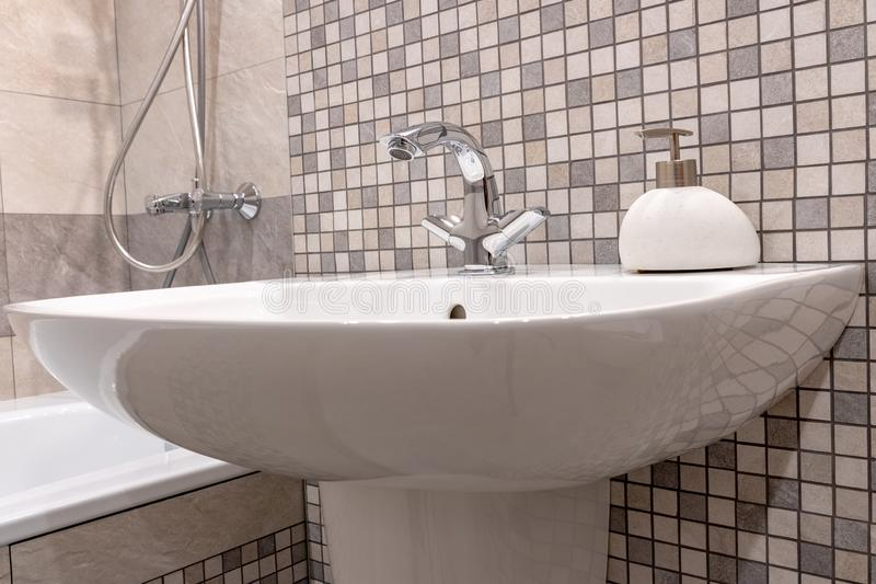 White clean bathroom sink with shiny faucet and stone soap dish. stock photos