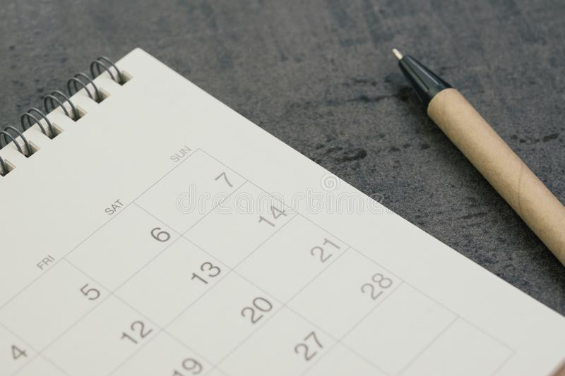 White clean calendar with pen on dark blackboard desk using as reminder, plan or personal diary concept royalty free stock images