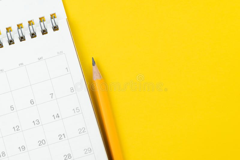 White clean calendar with yellow pencil on solid yellow background with copy space using as reminder, schedule or business project stock image