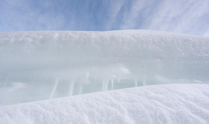 White clean snowdrifts and icicles close-up. Pile of snow. White snow close-up. Snowdrifts and icicles close-up. Frozen snow in a pile. Winter background royalty free stock photography