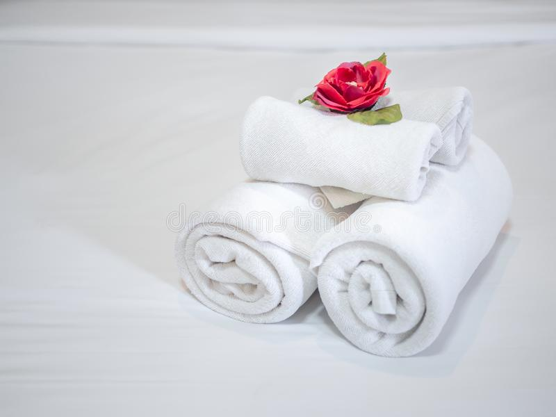 White clean towels decoration with red flower on white clean bed in hotel room. Close-up white clean towels decoration with red flower on white clean bed in royalty free stock images