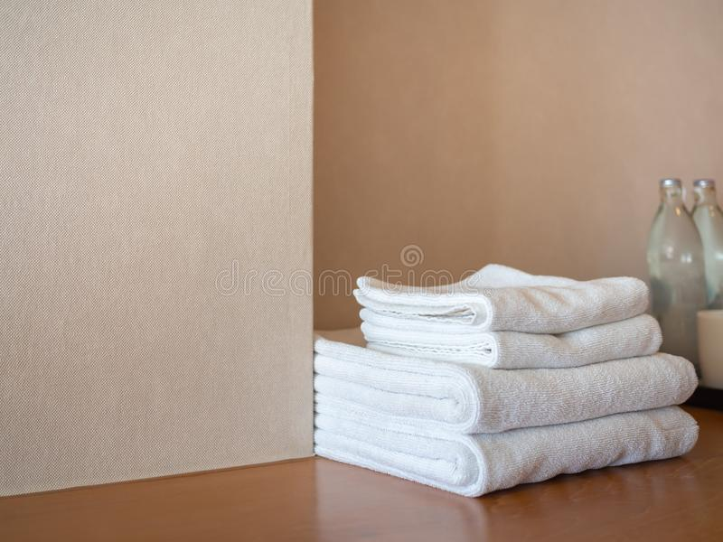 White clean towels on wooden surface and white wall background. White clean towels and bottle of drinking water on wooden surface and white wall background in royalty free stock images