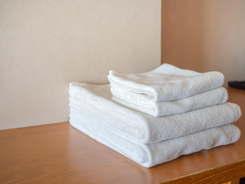 White clean towels on wooden surface and white wall background. With copy space royalty free stock photography