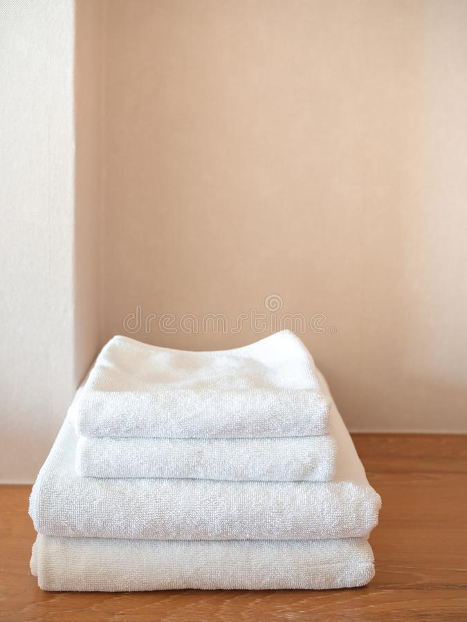 White clean towels on wooden surface and white wall background. With copy space vertical style royalty free stock photography