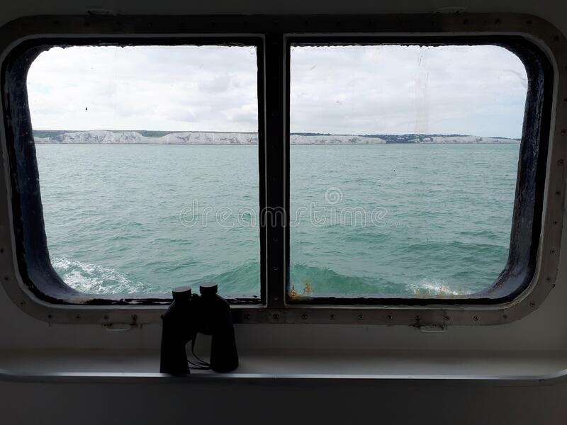 White Cliffs of Dover through grungy ship`s window. A view of the sea and the White Cliffs of Dover through a grungy dirty ship`s window with binoculars stock photo