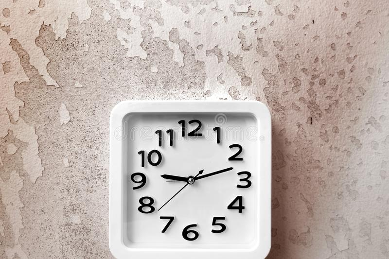 White Clock Isolated. Time Nine Alarm Clock on Old Brown Crack Wall Background stock images