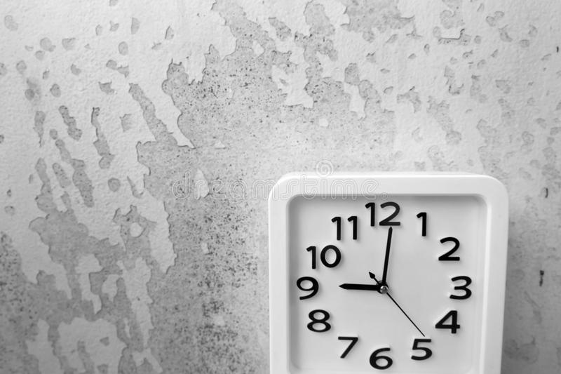 White Clock . Time Nine Alarm Clock on Old Gray Crack Wall Background royalty free stock photo