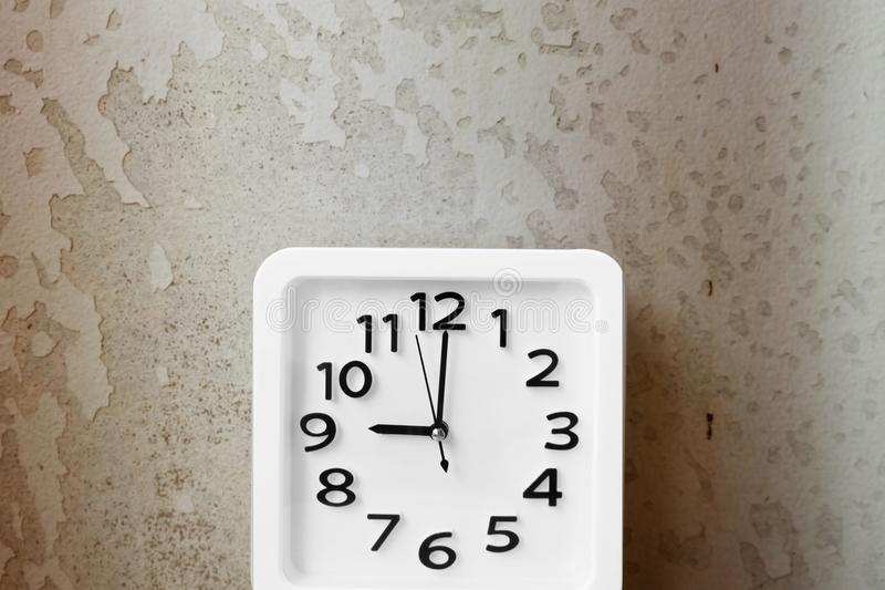 White Clock . Time Nine Alarm Clock on Old Brown Crack Wall Background royalty free stock photography