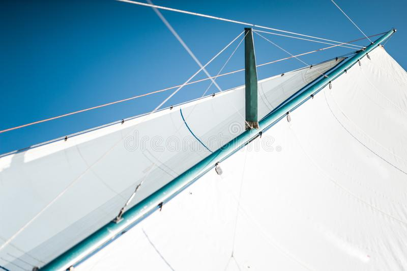 White cloth fabric, masts and ropes close-up on the sail of tri-yacht or yacht sailing boat. White cloth fabric, masts and ropes close-up on the sail of a tri stock images