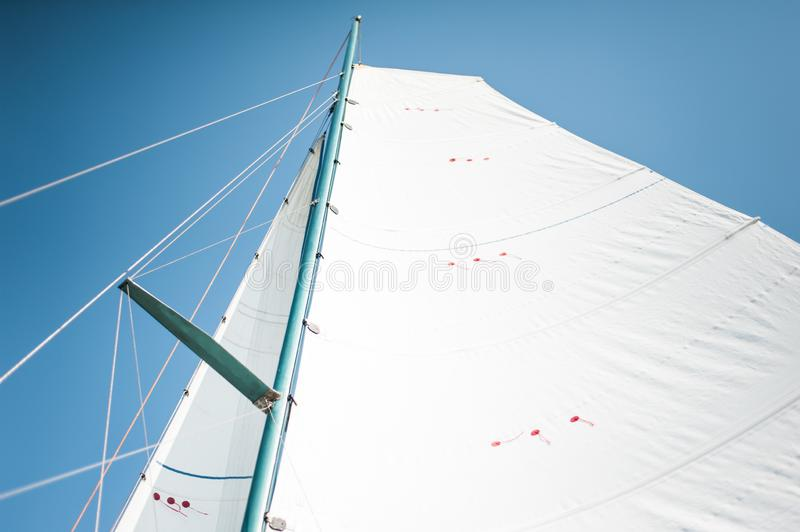 White cloth fabric, masts and ropes close-up on the sail of tri-yacht or yacht sailing boat. White cloth fabric, masts and ropes close-up on the sail of a tri stock photos