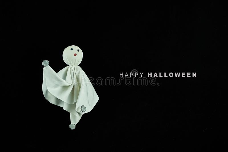 A white cloth ghost next to a happy halloween lyrics. The background is black. Party concept royalty free stock photography