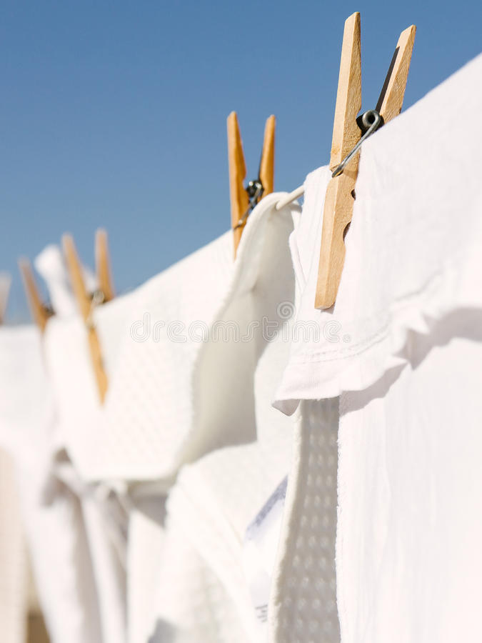 White clothes hung out to dry in the bright warm sun. White clothes hung out to dry on a washing line in the bright warm sun. Background is a clear blue sky royalty free stock photography