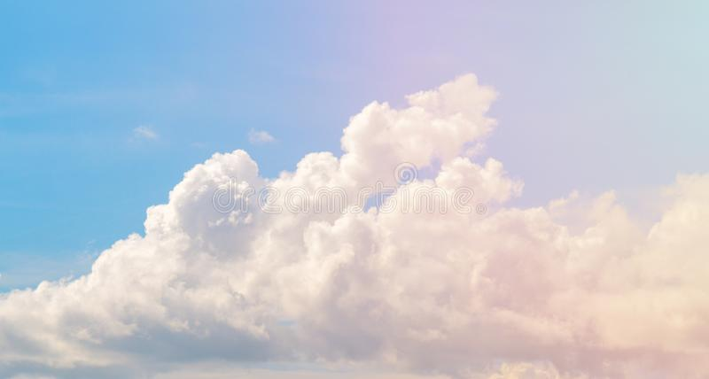 White cloud on blue sky. Cloudscape photo background. Romantic skyscape with cloud and pink sun flare. royalty free stock photography