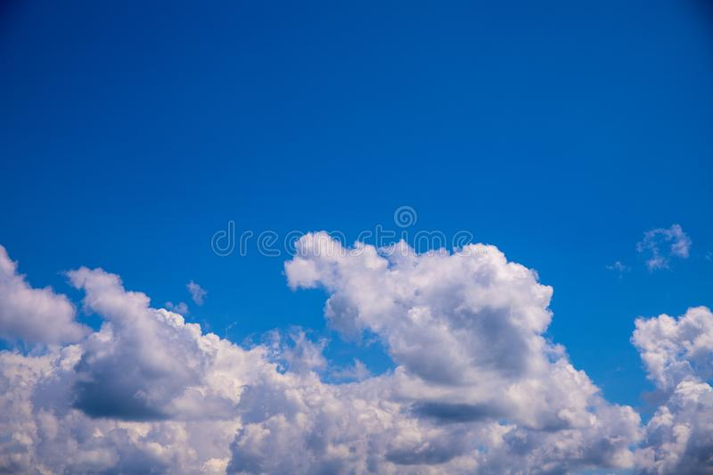 White cloud and clear blue sky above. Sunny cloudscape photo background. Skyscape with fluffy clouds royalty free stock photography