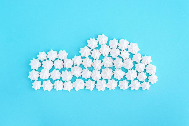 White cloud made of meringues on blue background. Weather concept stock photos