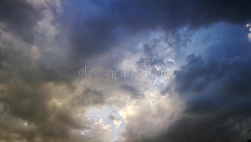 White cloud surrounding with scattered black cloud with blue sky background. Cof, cloudscape, skyscape, rainy, season, bright, sunlight royalty free stock photos