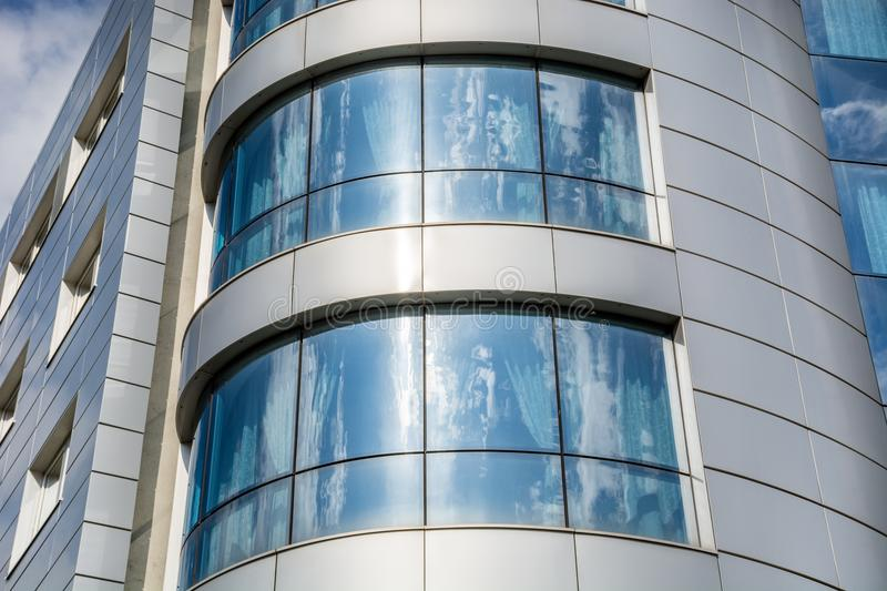 Clouds and sky reflected in windows on modern office building royalty free stock photo
