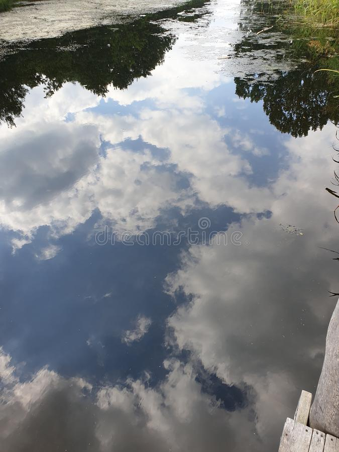 White clouds and blue sky reflecting on the water surface in Capelle aan den IJssel in Park Hitland. stock images