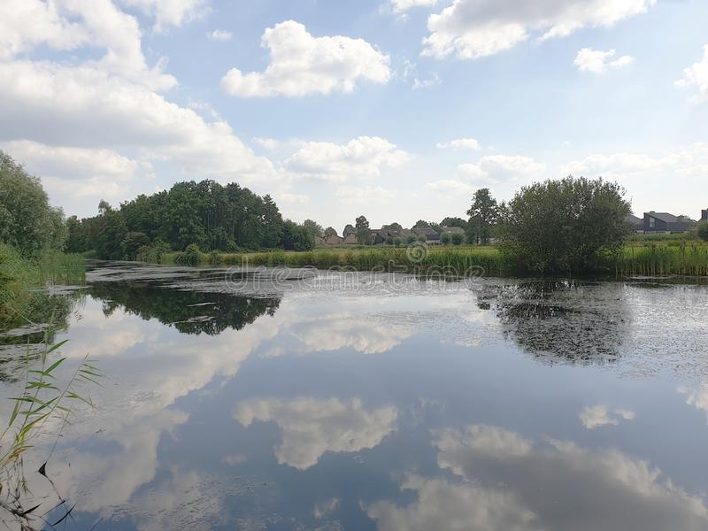 White clouds and blue sky reflecting on the water surface in Capelle aan den IJssel in Park Hitland. royalty free stock images