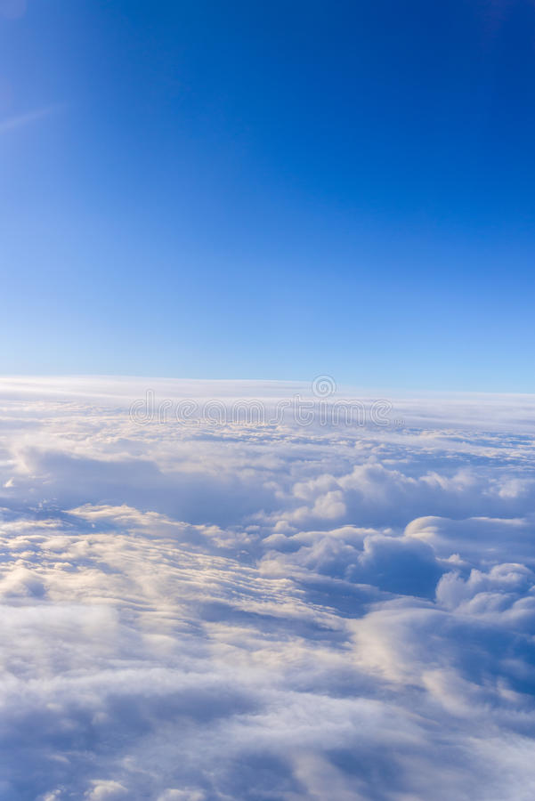 White clouds and blue sky skyscraper. view from the window of an. Airplane flying in the clouds, top view clouds like the sea of clouds sky background royalty free stock images