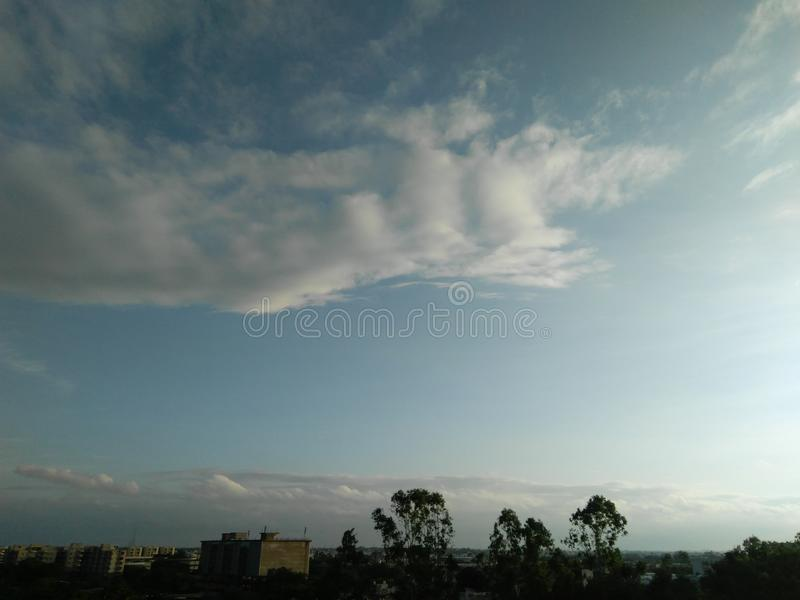 White clouds in the blue sky, view of cityscapes, skyscapes, skylines, trees, building and cityscapes. Nature, photography, natural, scenery stock photo