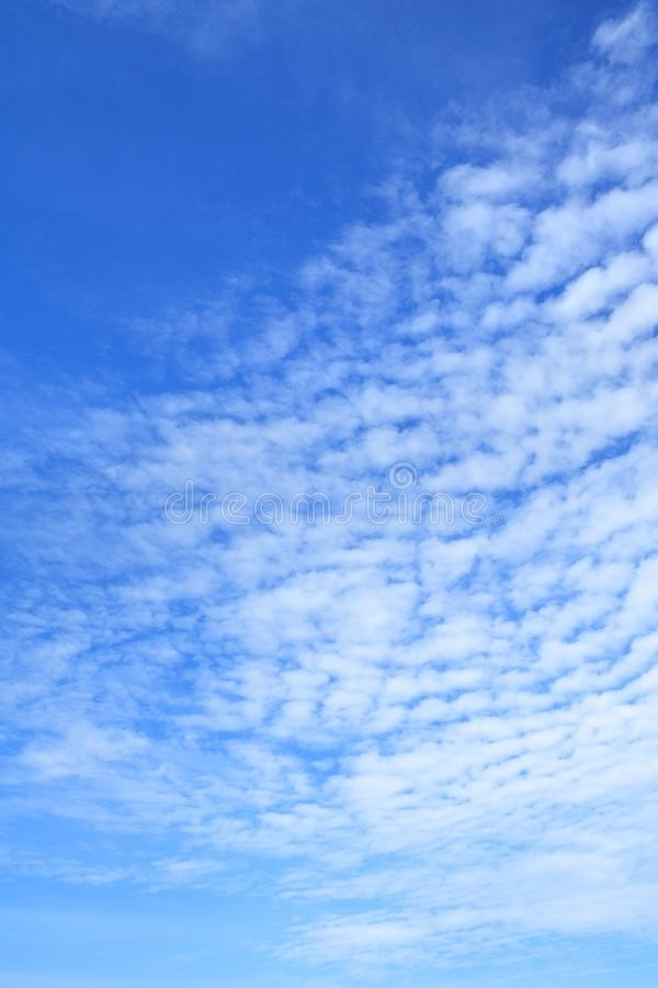 White clouds in azure sky as background. White clouds in bright azure sky as background vertical image orientation royalty free stock photo