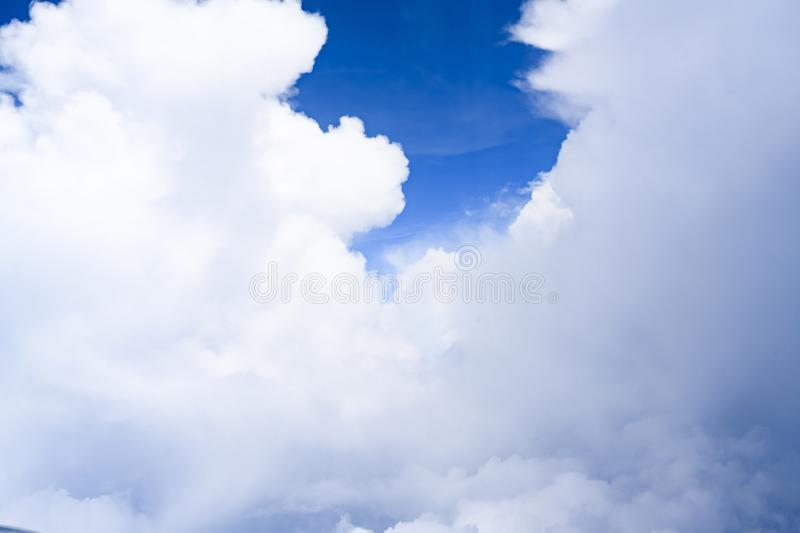 White clouds building tower or wall with small view through hole to blue sky, cloud in bright sky seen from plane stock photography