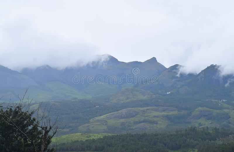White Clouds descending over Green Mountains of Western Ghats - Munnar, Idukki, Kerala, India. This is a photograph of white clouds covering peaks of green stock images