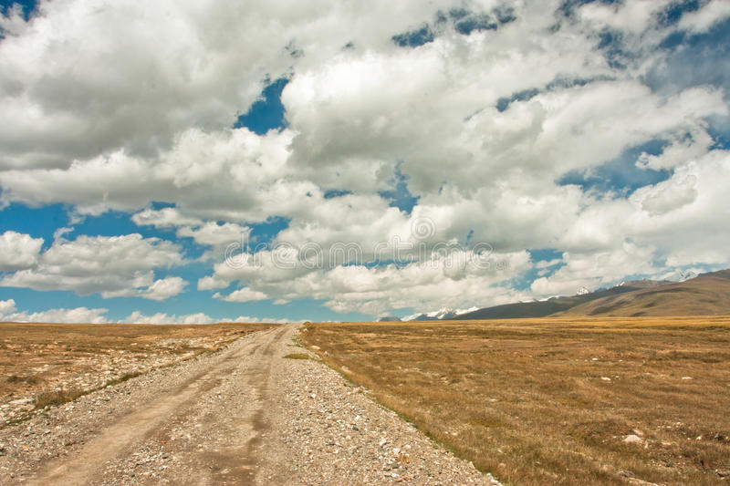 White clouds floating over rural mountain road stock photography
