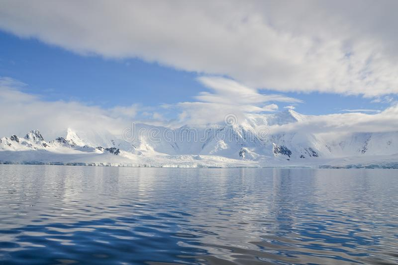 Water lay still under low hanging white clouds that cover Antarctic mountains. White clouds hang over the snowcapped mountains over still waters in Antarctica royalty free stock images