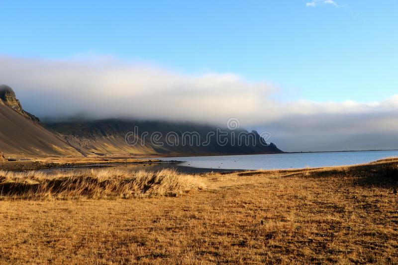 White clouds hanging on the black mountains near Hofn in Iceland. stock images