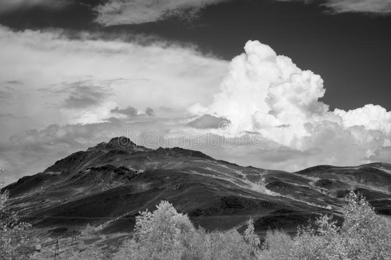 White clouds over the mountains of Karabash. IR photo. Snow-white clouds over the black mountains of the city of Karabash. IR photo royalty free stock image
