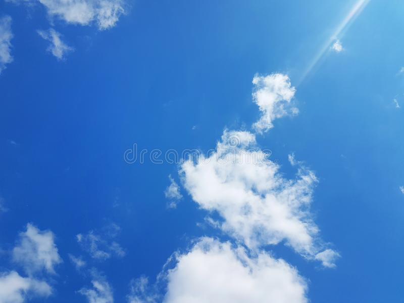 White clouds on a sunny blue sky stock photos