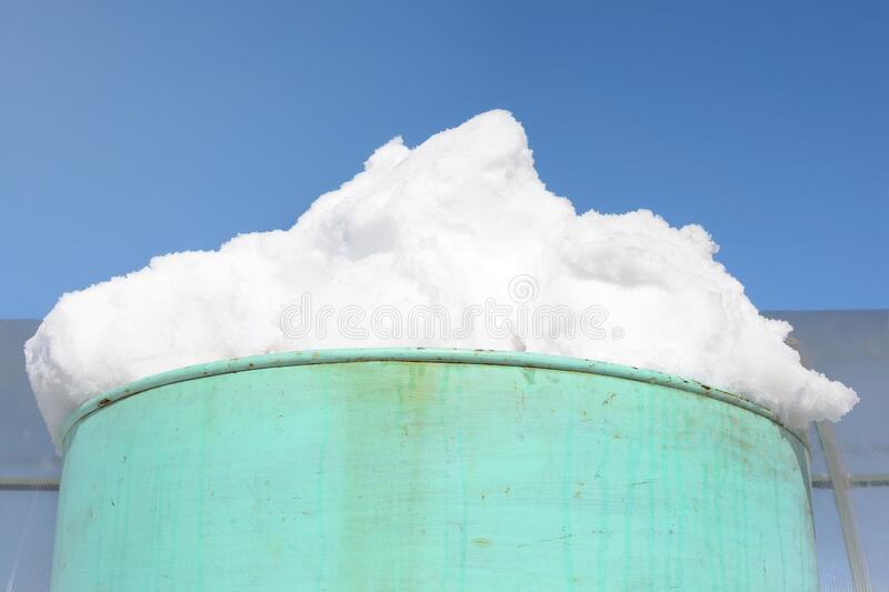 White clumps of snow in a barrel against a blue sky. Spring work in the country stock photo