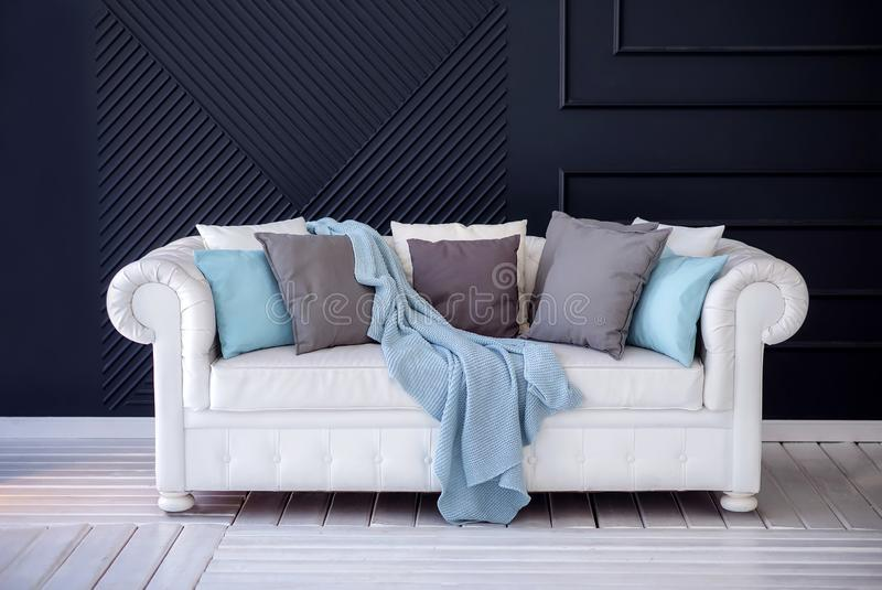White coach with a grey and blue pillows and woolen blanket standing on a white wooden floor against dark blue wall. White coach with a grey and blue cushions stock photo