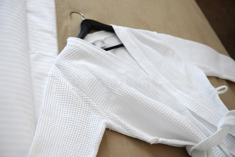White coat on the bed. In the hotel stock images