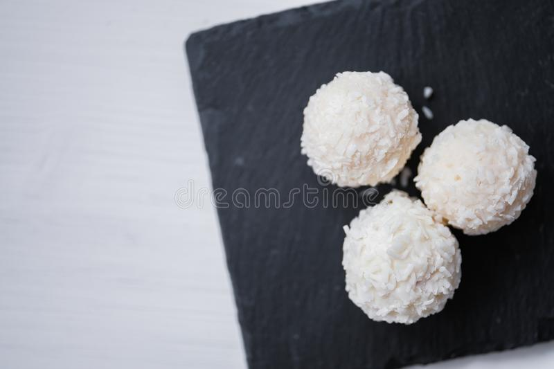 White coconut candy balls in plate shale dishes on rustic wooden background. Top view. Copy space. Right side stock photography
