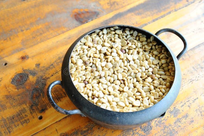 White coffee bean in vintage steel bucket on wooden table. White coffee bean in vintage steel bucket putting on wooden table stock photography
