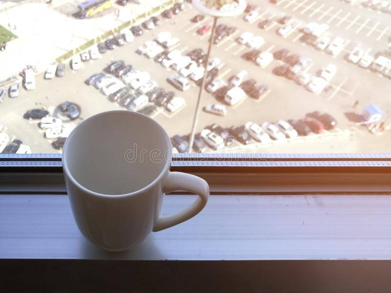 White coffee cup on aluminum window sill. stock photos