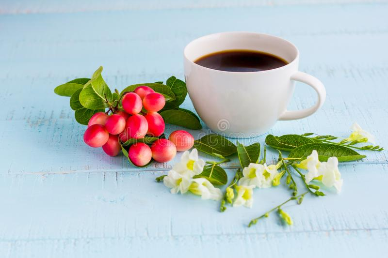 White coffee cup with black coffee ,flowers and fruits. On wooden table stock photos