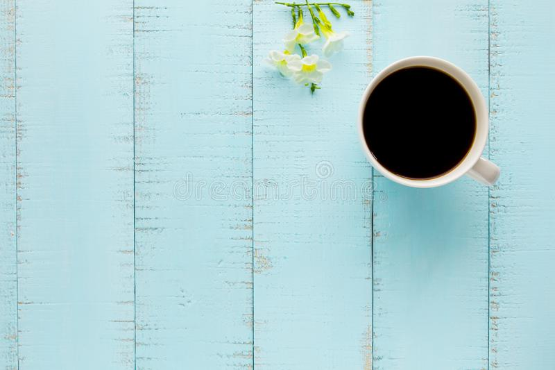 White coffee cup with black coffee and flowers. On wooden table royalty free stock photo