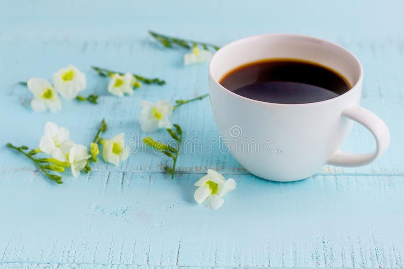 White coffee cup with black coffee and flowers. On wooden table stock image