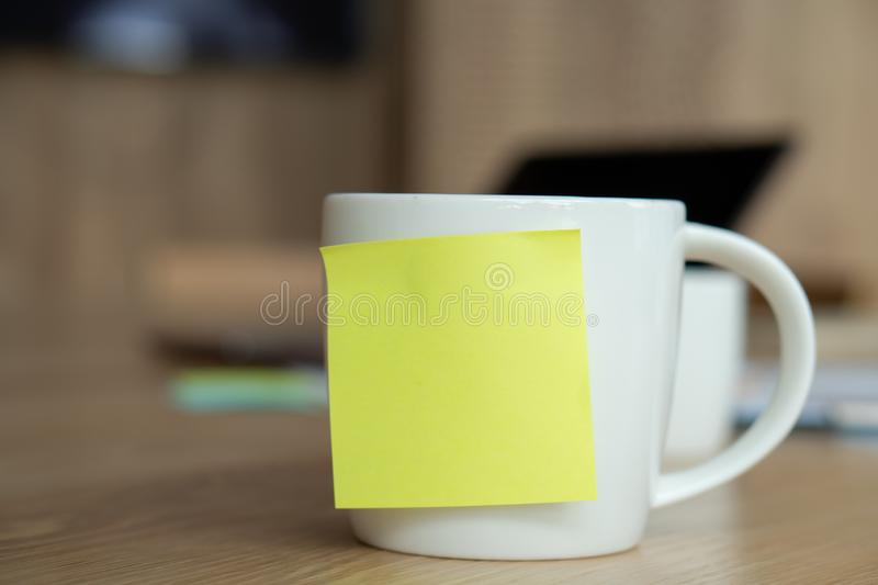 A white coffee cup with a blank yellow post-it on the cup. Resting on the desk and laptop is placed on the back stock image