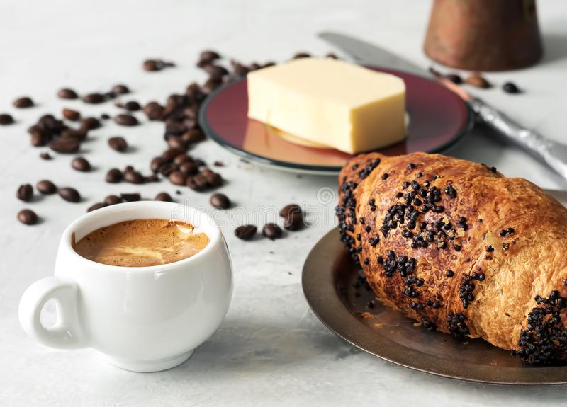 White coffee cup with espresso and croissant. Nearby are fresh coffee beans, butter and cezve. Located on a gray background. Close. Up royalty free stock photography