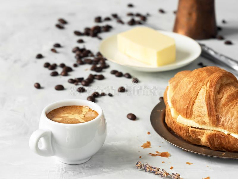 White coffee cup with espresso and croissant. Nearby are fresh coffee beans, butter and cezve. Located on a gray background. Close. Up royalty free stock photos