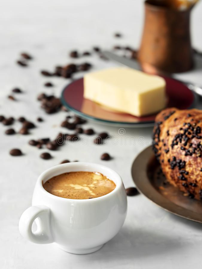 White coffee cup with espresso and croissant. Nearby are fresh coffee beans, butter and cezve. Located on a gray background. Close. Up stock image