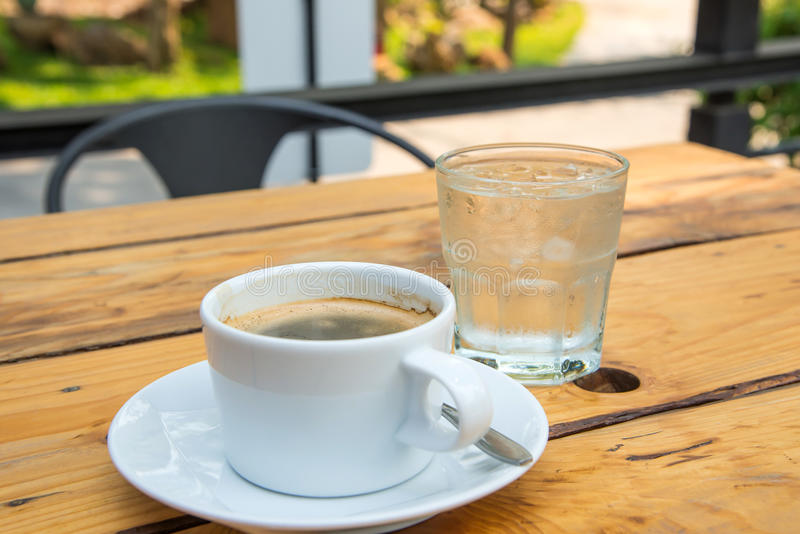 White coffee cup,Glass water on wooden floor. royalty free stock image
